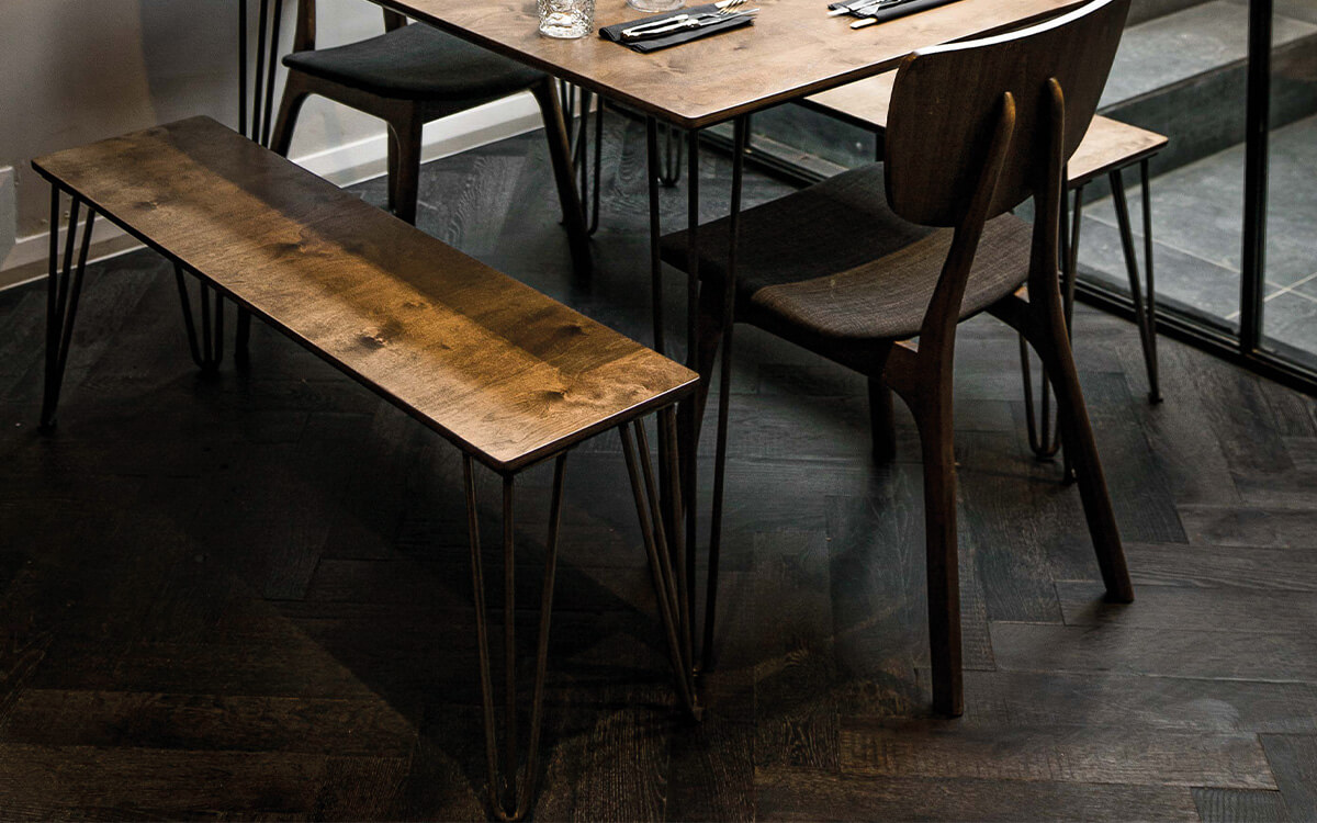 A clos up of the wooden tables and chairs set against our black Ebony superwide parquet floor
