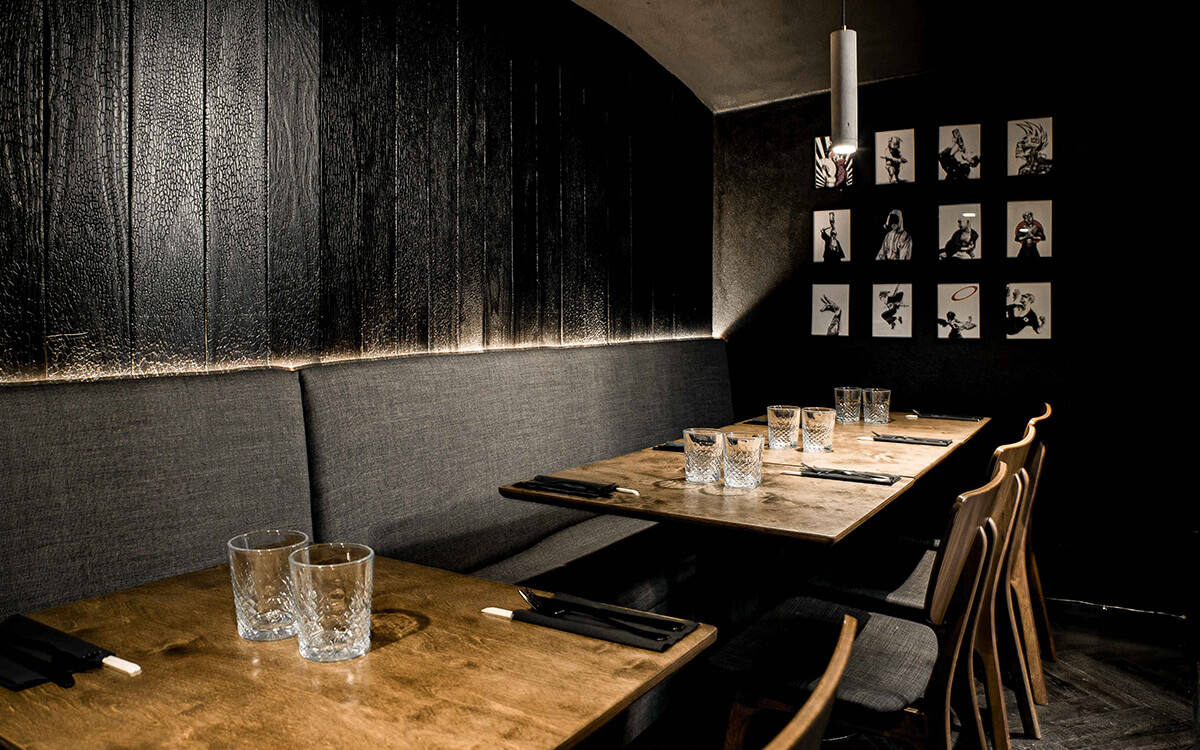 A inimate seating area of tables with benches set against dark textured wood walls